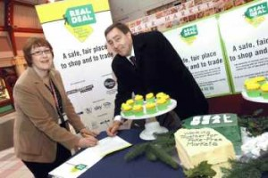 Heather Thurlaway, Operations Manager Markets, and David Ellerington, Trading Standards Team Manager, celebrate the Charter signing with a large Real Deal cake, specially baked for the occasion by The French Oven and cupcakes by Pet Lamb Patisserie ˆ both are stalls in the Grainger Market.